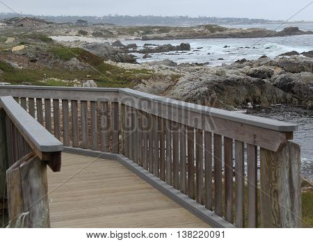 Wooden footbridge alongside shoreline of sandy beaches, patches of green foliage,and jagged rocks with grey blue water and waves of white foam in Pacific Grove, California on an overcast day.