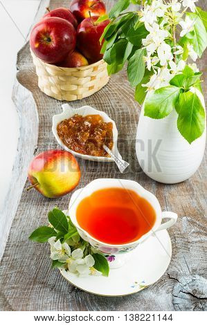 Cup of tea and apple jam on rustic wooden table. Homemade apple marmalade for tea time. Breakfast tea with sweet apple confiture.