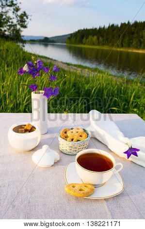Evening tea sunset river view. Cup of tea and cookies in small wicker basket with blue bell flowers in vase. Summer tea time concept.