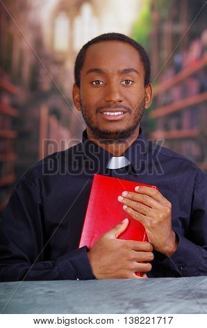 Catholic priest wearing traditional clerical collar shirt sitting and holding bible looking into camera, religion concept.