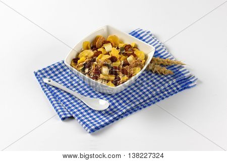 bowl of corn flakes and cereals on checkered dishtowel