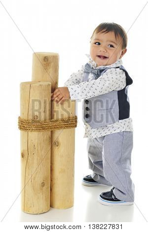 An adorable, dressed up baby boy holding on 3 mooring posts as he steadies himself for standing.  On a white background.