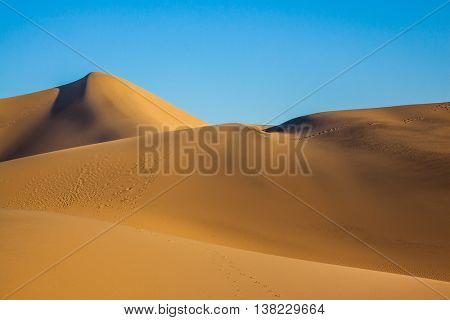 Sunny morning in a picturesque part of Death Valley, USA. Mesquite Flat Sand Dunes. Bizarre twists of orange sand dunes