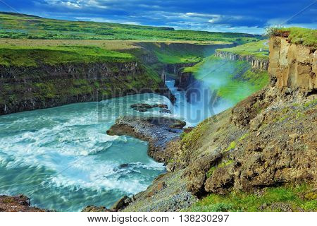 Fantastically spectacular cascading waterfall Gyullfoss. Roaring water glistens on the northern sun. Iceland in the summer