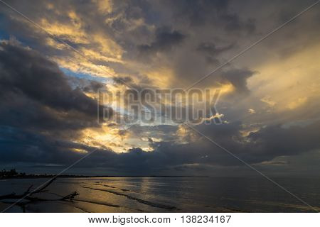 Dramatic sunset with clouds on the ocean coast. Sun rays in the clouds. Fiji.