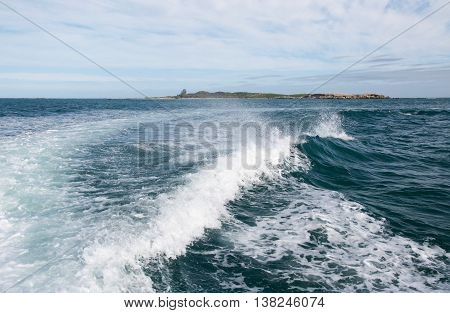 Foamy waves from a boat wake in the Indian Ocean waters under an overcast sky in Rockingham, Western Australia.