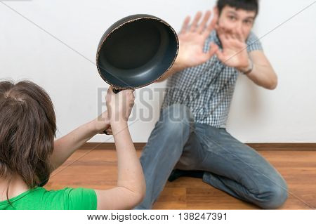 Wife Is Attacking Her Husband With A Frying Pan. Domestic Violen