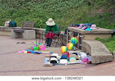DURBAN SOUTH AFRICA - JULY 09 2016: Beach vendor on the promenade near the the Millennium Pier and lighthouse in Umhlanga Rocks