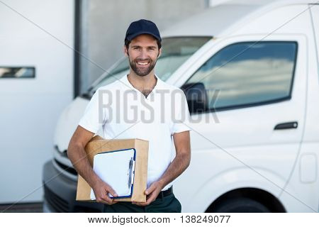 Portrait of delivery man is holding cardboard box and posing in front of a warehouse