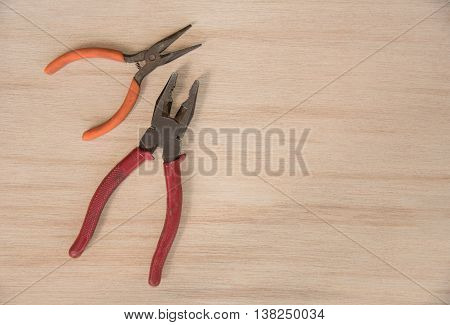 work tools hammer wrench screwdriver pincers pliers hand screw pliers old spanner on a wooden table top view with empty space