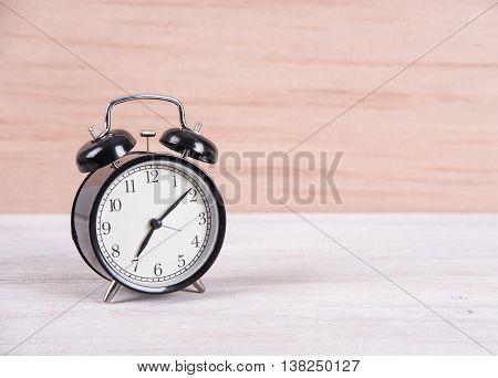 black alarm clock on old woodden table background.vintage tone