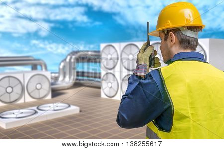 HVAC (Heating Ventilating Air Conditioning) maintenance concept. Conditioner units on roof of building and worker.