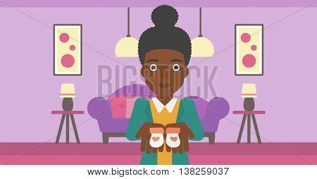 An african-american pregnant woman holding baby booties in hands on the background of living room. Vector flat design illustration. Horizontal layout.