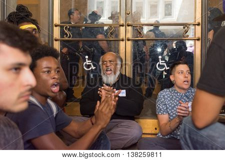 Black Lives Matter Protestors  Sit In Front Of An Entrance Of The City Hall