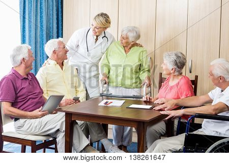 Seniors with wheelchair and walking aid in a retirement home