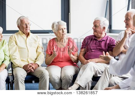 Seniors and nurse talking to each other in a retirement home