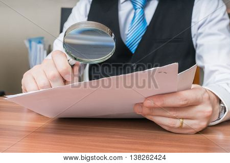 Laywer Is Analysing Document With Magnifying Glass.