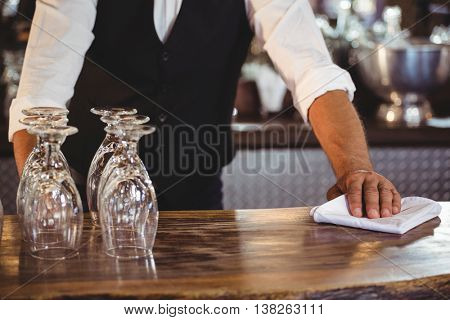 Mid section of bartender cleaning a bar counter with napkin
