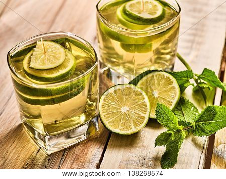Alcohol cocktail . Wooden boards two glasses with alcohol green transparent drink. A drink number hundred forty one mojito cocktail with half lime and mint . Top view. Country life. Light background.