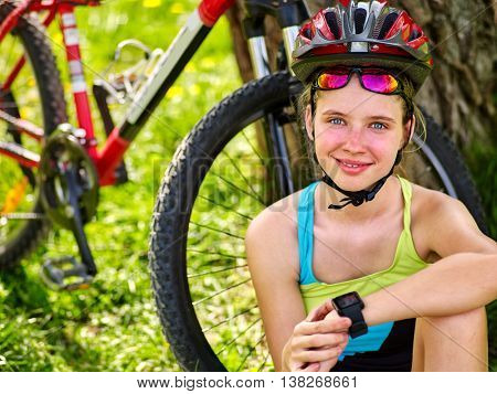 Bikes cycling girl. Bicyclist girl with smart watch on hand. Girl counts pulse after bicycle training. Cycling is good for health.