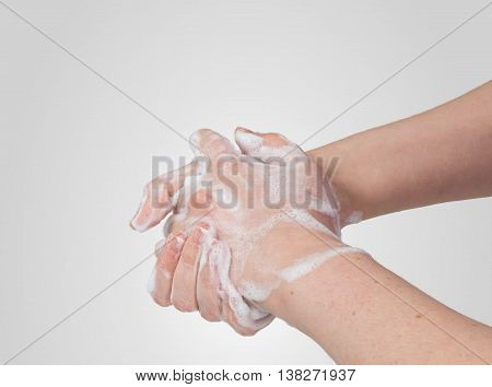 Washing or cleaning hands with soap on gray background.