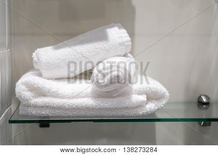 Three towels are placed on the shelf in the bathroom