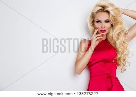 Very Beautiful Sexy Blond-haired Woman Girl In A Sexy Short Red Dress Crystals With Long Legs Standi