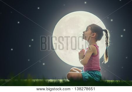 cute little child girl enjoying meditation and yoga on green grass on moon sky background