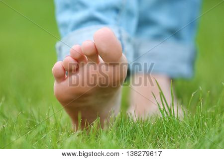 Woman walking barefoot  on green grass background