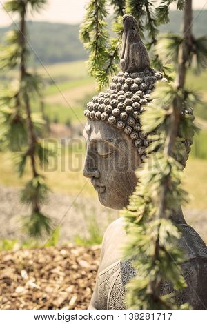 Garden decoration with a lying buddha on a sunny day