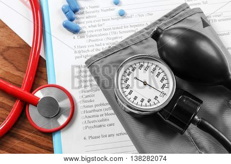Medical concept. Medical stethoscope and manometer with patient history, close up