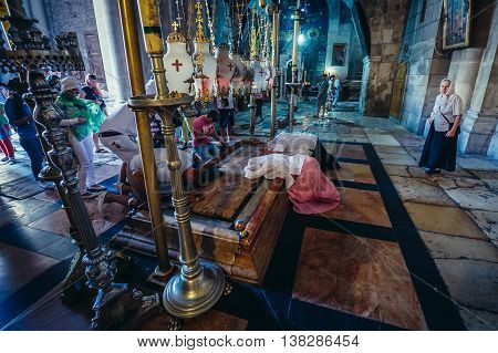 Jerusalem Israel - October 22 2015. A Christian pilgrims prays on the Stone of the Anointing inside the Church of the Holy Sepulchre located in Christian Quarter