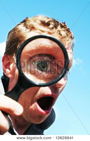 Astonished man see through magnifying glass