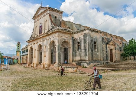 TRINIDAD, CUBA - SEPTEMBER 28, 2007: Man with bicycle in front of the Church of the Holy Trinity in Trinidad, Cuba