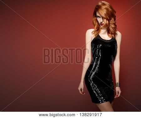 Fashion woman in Glamour Sequin black dress. Stylish Luxury party Outfit. Redhead sexy Model girl, Trendy wavy Fashion Hairstyle on red.Fashion party Makeup, shiny fashion Accessories.Unusual creative
