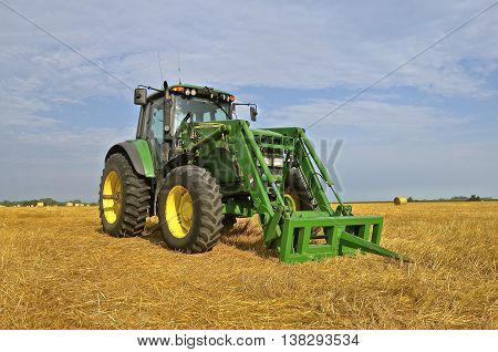 ROSHOLT, SOUTH DAKOTA; August 15, 2015: The new tractor and spear bale loader are products of John Deere Co, an American corporation that manufactures agricultural, construction, forestry machinery, diesel engines, and drivetrains.