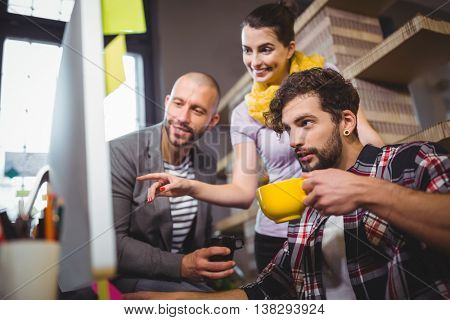 Businesswoman pointing at computer desktop while explaining male colleagues in creative office