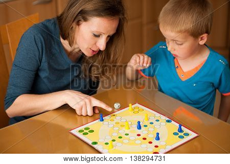 mother and young poy play ludo game in living room