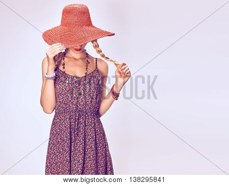 Hippie Boho woman Having Fun. Playful positive Model, Summer Fashion Outfit. Blonde in Trendy Sundress, pigtails, Fashion Accessories. Hat covers girl face, romantic fashion Style. Unusual creative