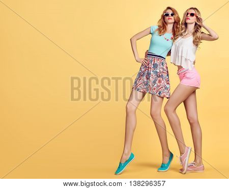 Fashion Hipster woman in Stylish Summer Outfit Having Fun. Hipster sisters best friends crazy cheeky Dance. Funny Girl in Fashion sunglasses. Glamour fashion Trendy Hairstyle, dancing.Unusual Creative