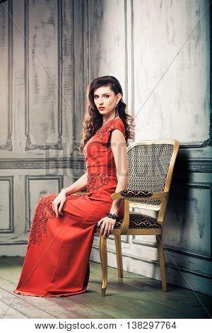 Beautiful sexy girl in red dress posing like diva in the studio