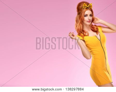 Fashion. Woman in Summer fashion dress, Pinup hairstyle, trendy fashion Makeup. Beauty sexy Redhead Model, glamor Stylish Fashion doll look. Playful model Pinup fashion girl on pink. Unusual creative