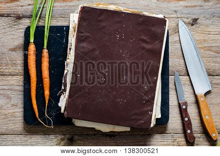 Vintage cook book. Old cook book with healthy recipes on wooden cutting board. Two young fresh carrots and two kitchen knifes on sides. Top view, copy space