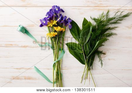 Bright colorful irises and herberas  in green ribbon on wood table. From above.