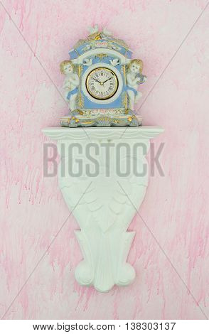 Pretty blue vintage porcelain clock with cherubs and doves on a carved white shelf against a pink background. Feminine shabby chic style. Vertical.