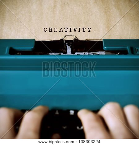 closeup of the hands of a young man typewriting the word creativity in a yellowish foil with an old blue typewriter