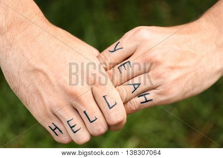 Man fists with fake tattoo on green grass background