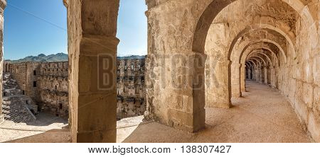 Panorama of top passageway in the theater of Aspendos including arcade and a view of amphitheater and environs through space between columns. Aspendos amphitheater is remarkably well preserved part of ancient Pamphylian and later Greco-Roman city of Aspen