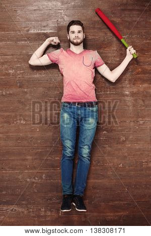 Top view photo of handsome young man on wooden floor. Man holding baseball bat