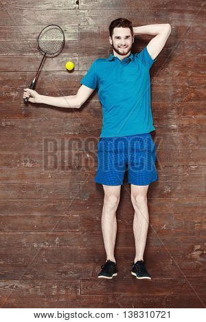 Top view photo of handsome young sportsman on wooden floor. Man with tennis racket